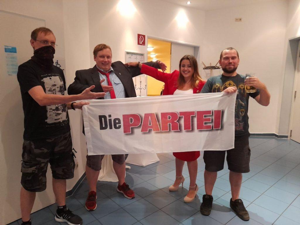 Vier Menschen, die mit einer PARTEI-Fahne posieren